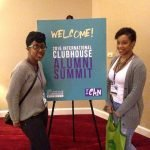 Two alumni pose next to a sign that says Alumni Summit