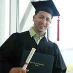 A young man in a cap and gown holding a diploma