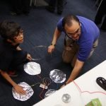 a clubhouse mentor and member work with a Makey Makey set