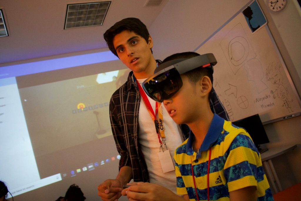 A mentor and member learn how to use virtual reality goggles