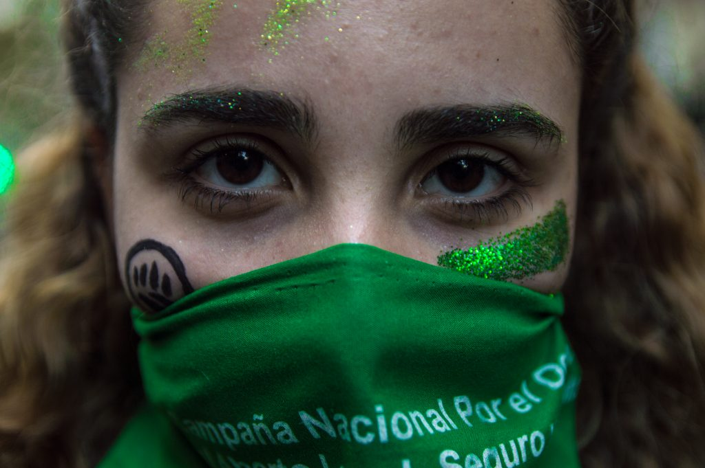 Close up photo of a young woman wearing a green handkerchief across her face