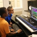 A mentor and member work together in the music studio