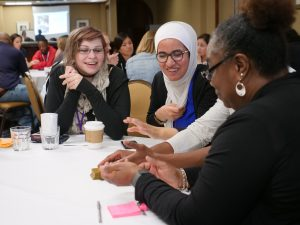A group of conference participants talk at a table