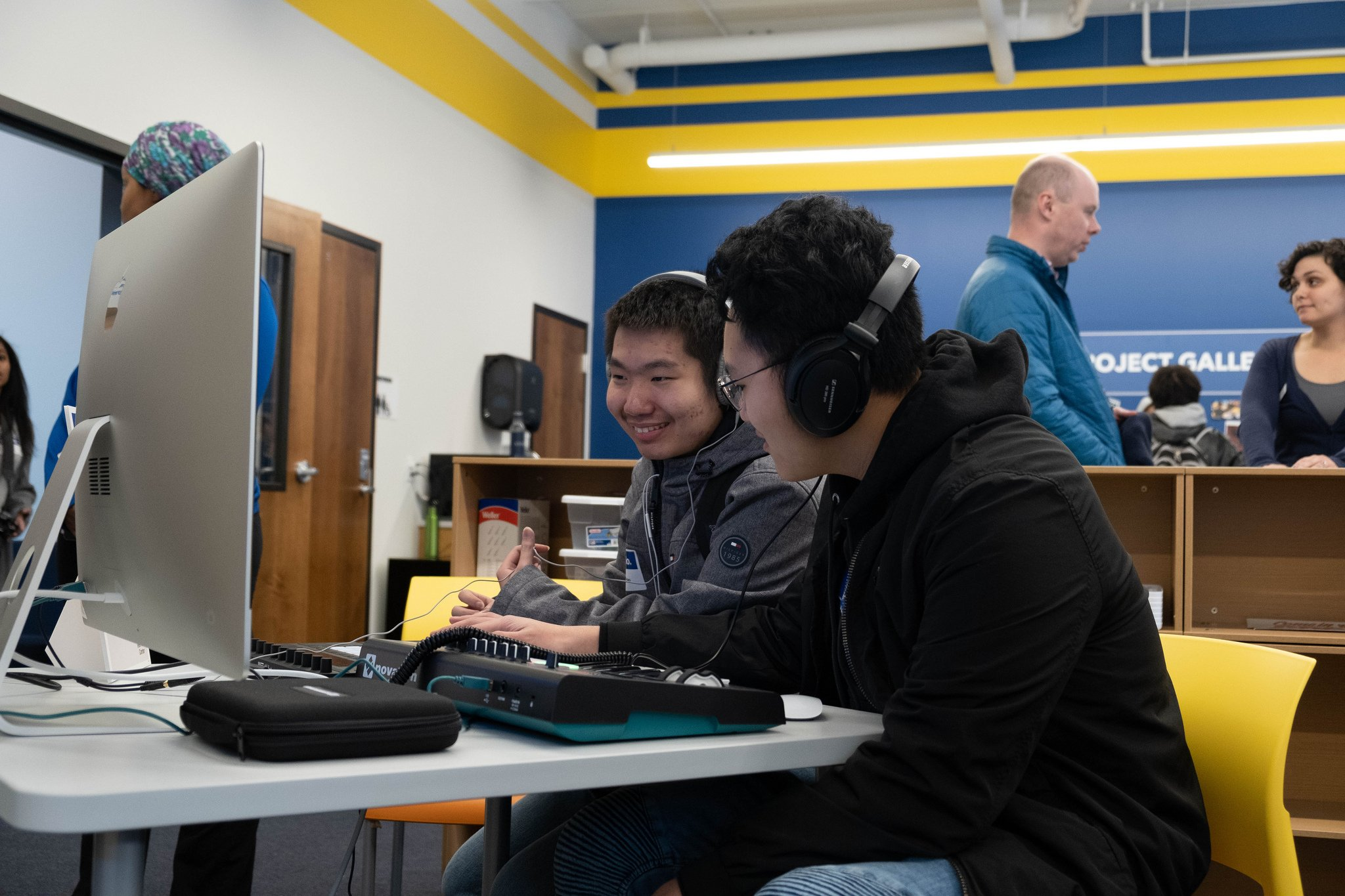 two young men work together at a computer audio workstation