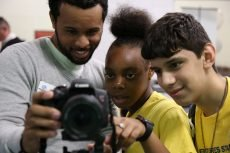 a mentor and two members look at a camera