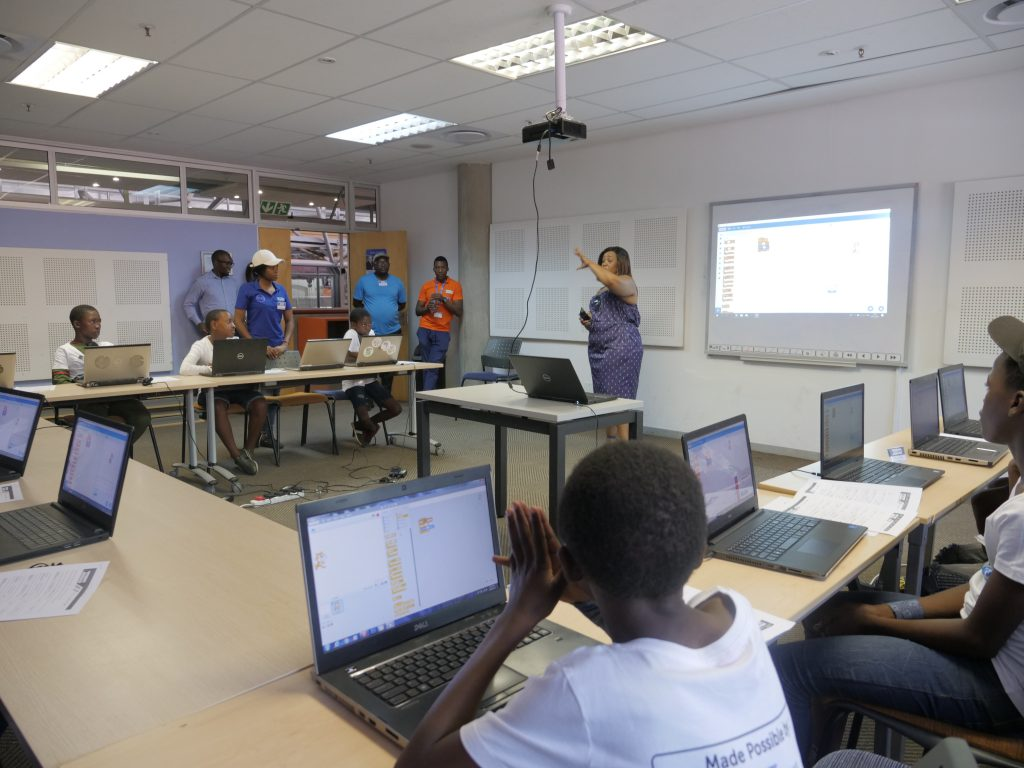 A woman gives a presentation to a class room of students at their computers