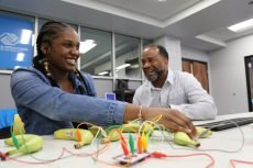 A young woman works with Makey Makey at a Teen Tech Center Grand Opening