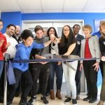 A group of youth and adults cut a ribbon with giant scissors at the Best buy Teen Tech Center Brooklyn Grand Opening