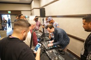 A group of conference attendees gather around DJ equipment