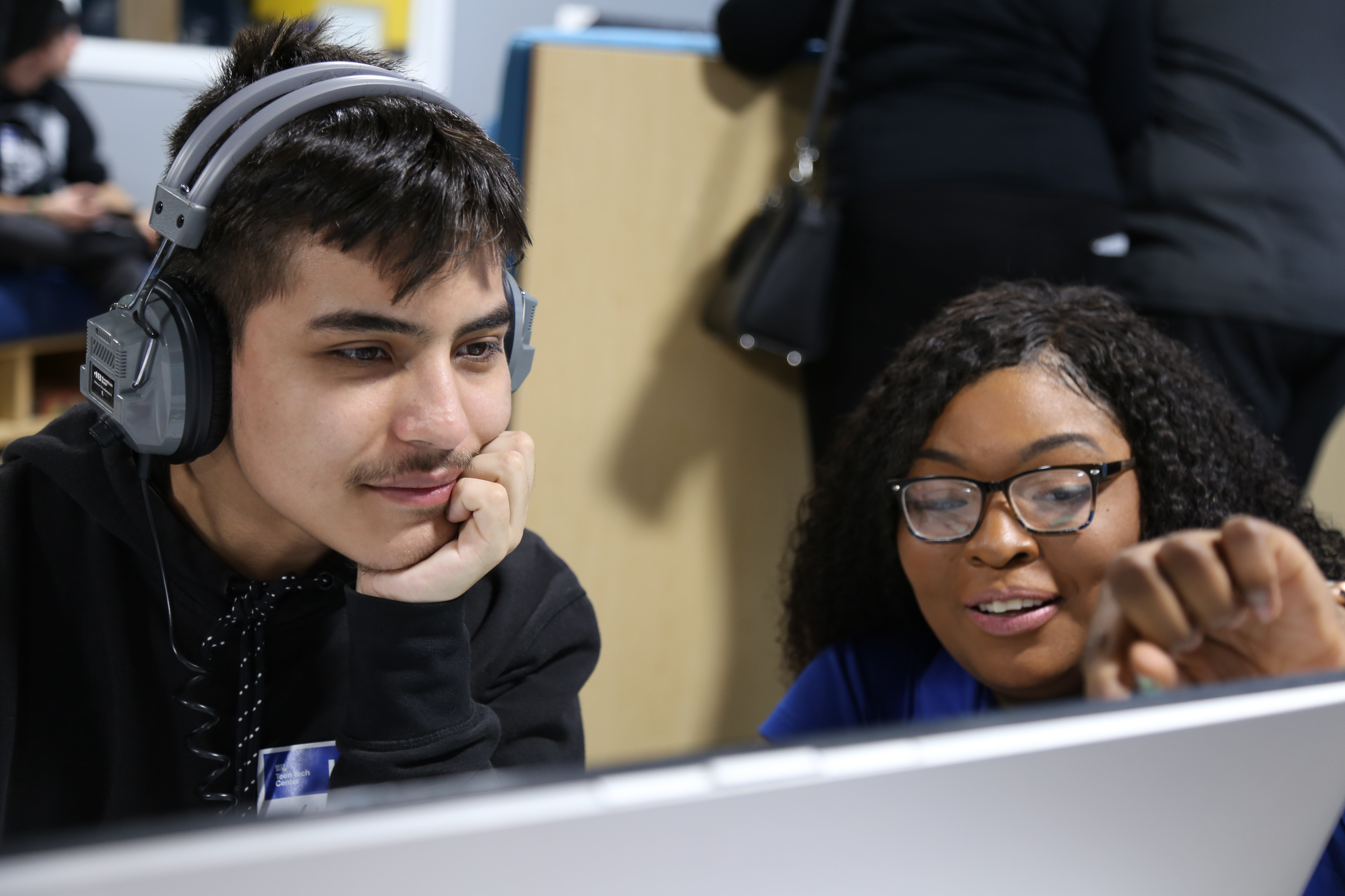 A woman helps a young man with a project in front of a computer