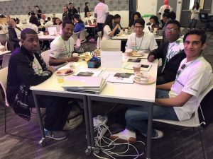 A group of teens work together at the Facebook Engineer for the Week Achievement summit