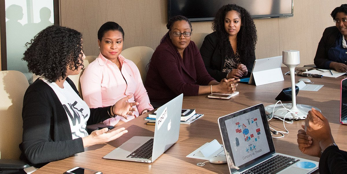 A group of professionals talk at a conference table.