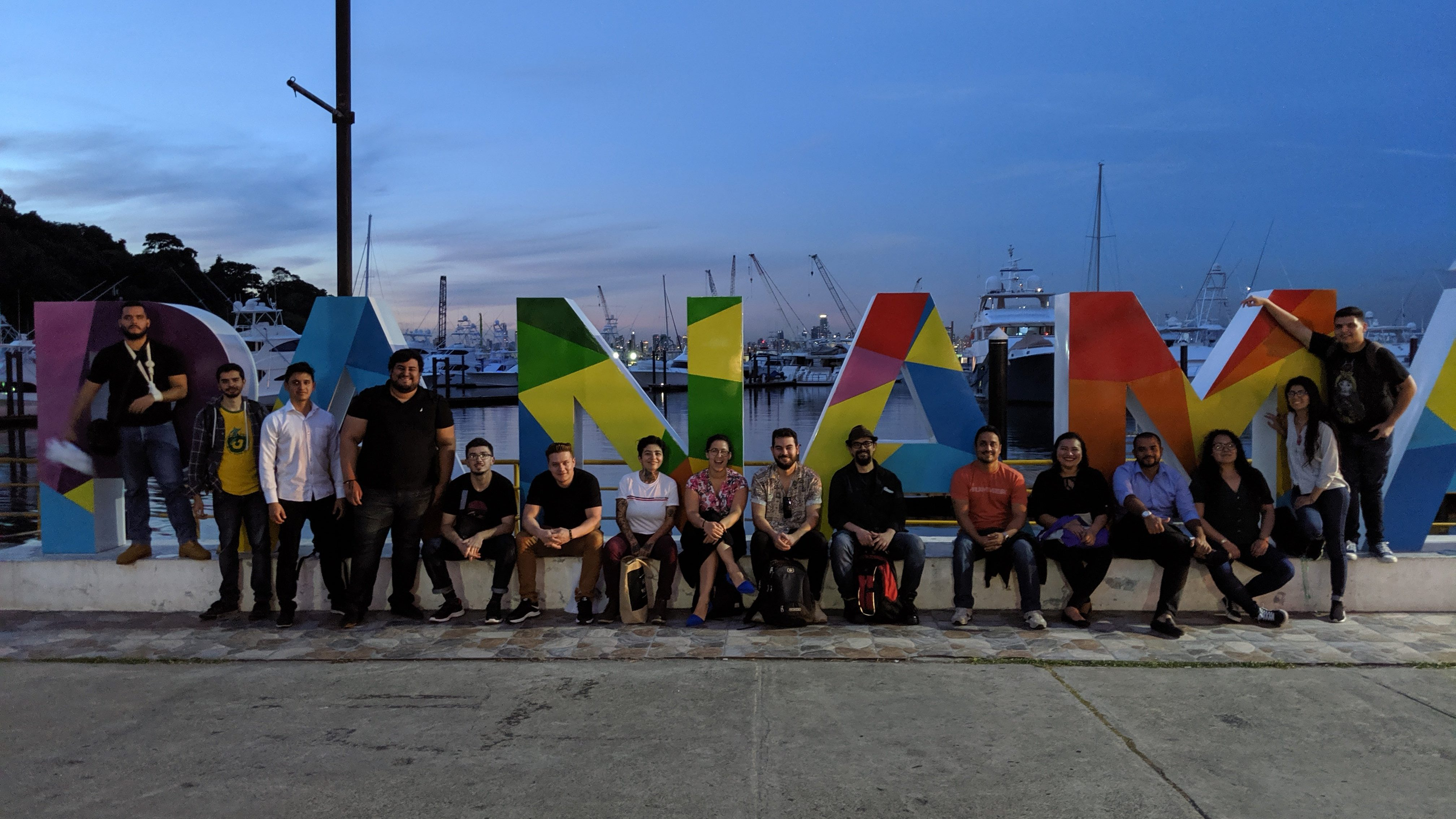 Clubhouse staff pose outside in front of public art that says 'Panama'