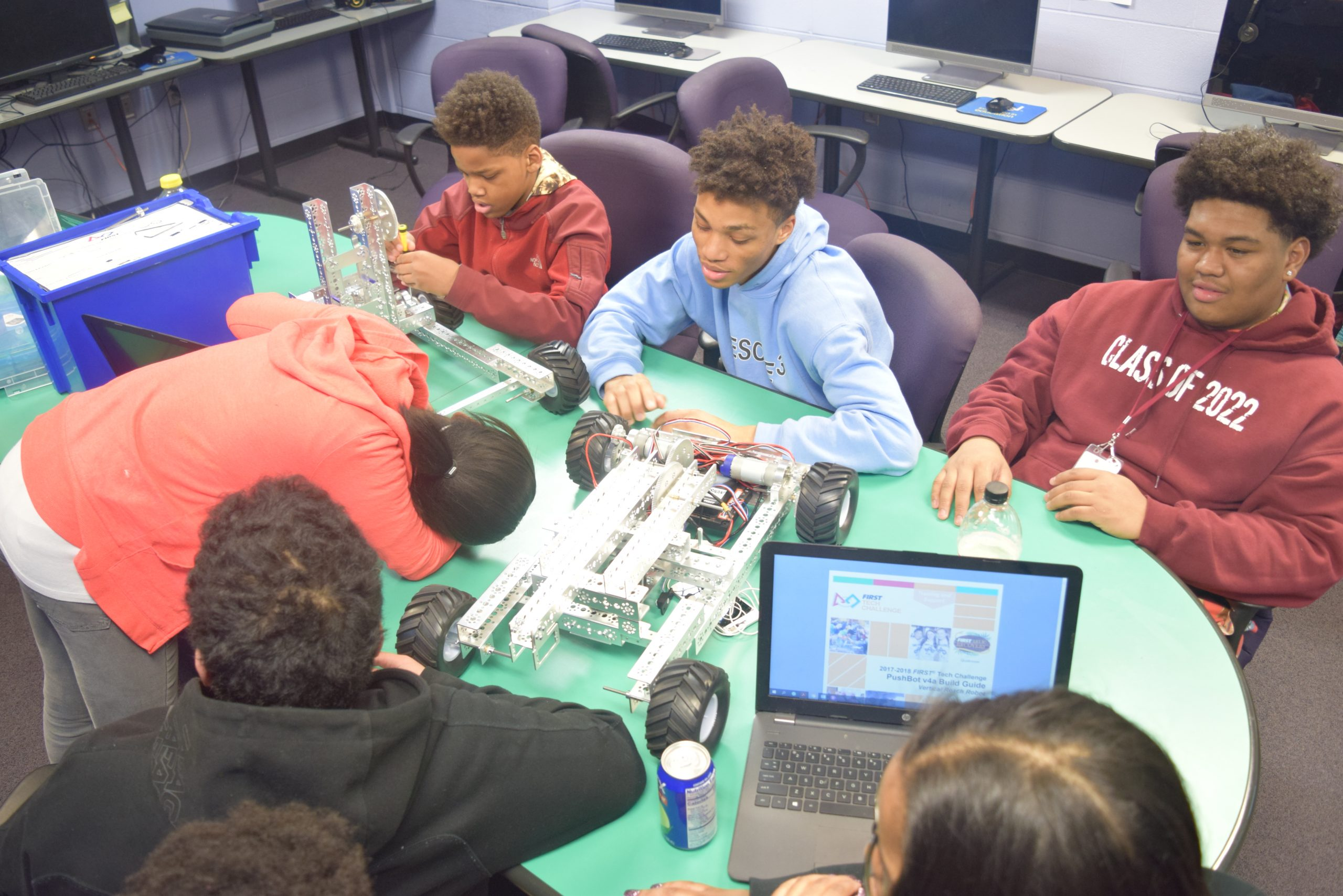 a group of youth work on a robotics project at a green table | Northwest Activities Center