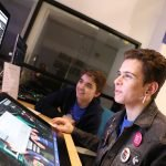 A youth and mentor use photoshop together at a computer.