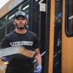 Chef Carlos Thomas carries a pan of food in front of a school bus